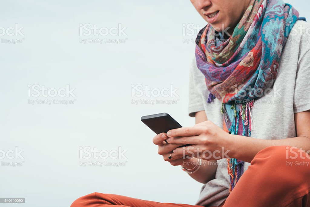 woman sitting, texting on phone outside on summer stock photo