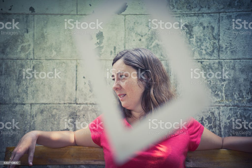 woman sitting under a tree with frames hanging from it stock photo