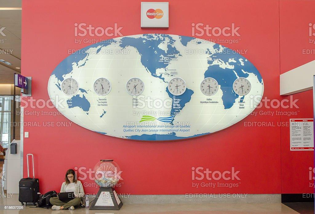 Woman sitting under large world map with international clocks stock photo