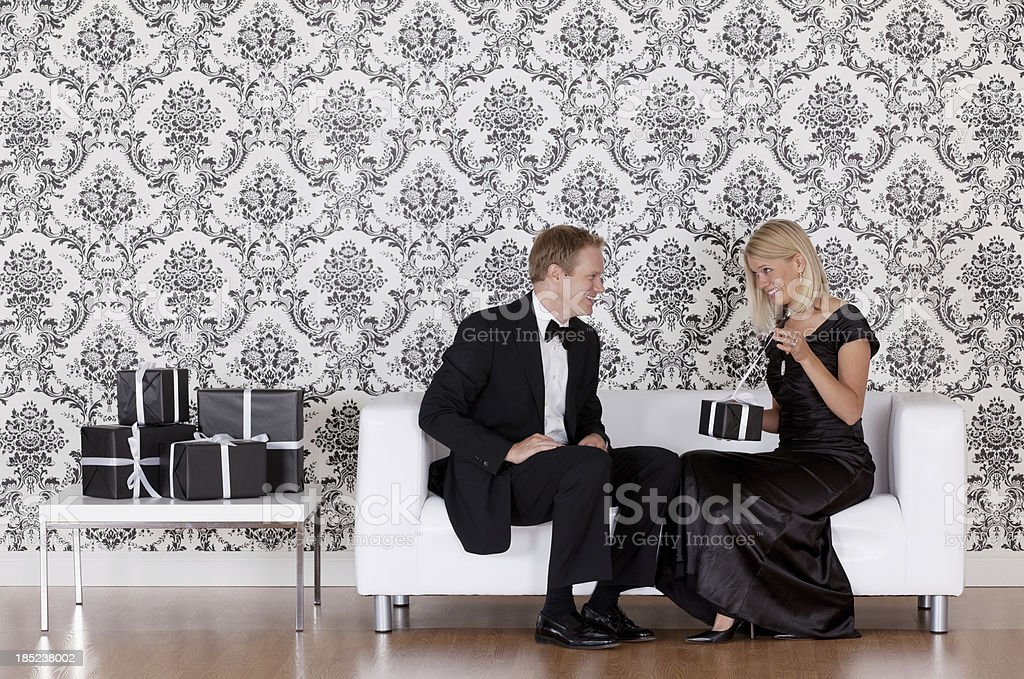 Woman sitting with a man opening present royalty-free stock photo