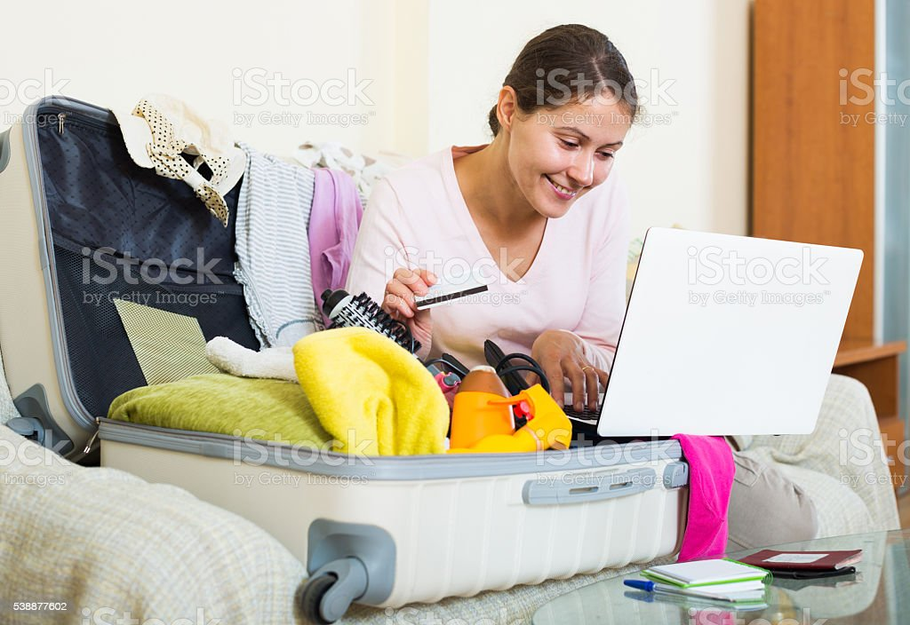 woman sitting with credit card near laptop and baggage stock photo