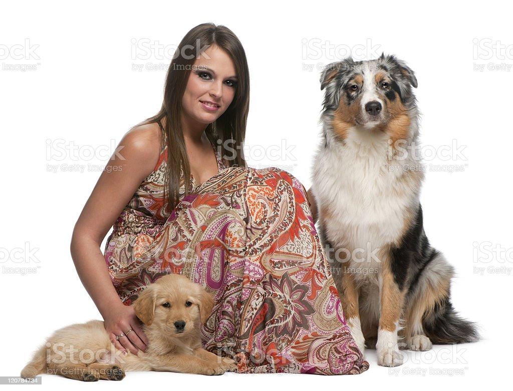 Woman sitting with Golden Retriever and Australian Shepherd, white background. royalty-free stock photo