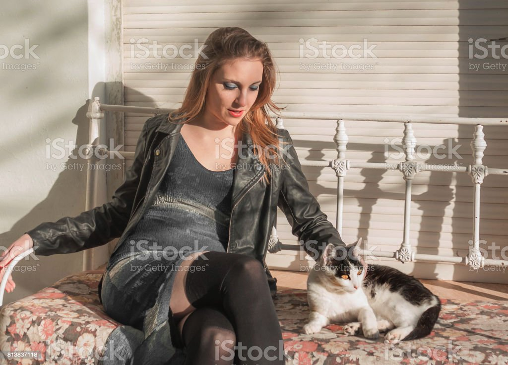 Woman sitting with kitten on the armchair stock photo