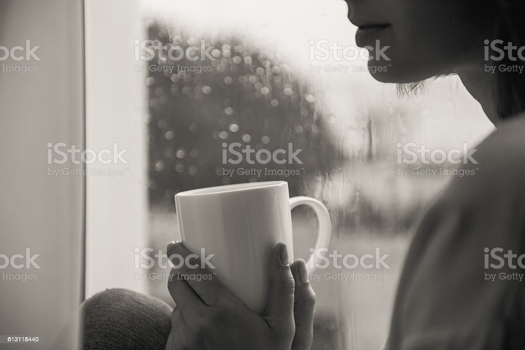 woman sitting with mug of tea by the window stock photo