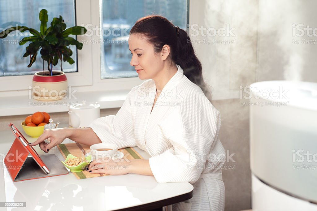 Woman sitting with tablet PC on the background of humidifier stock photo