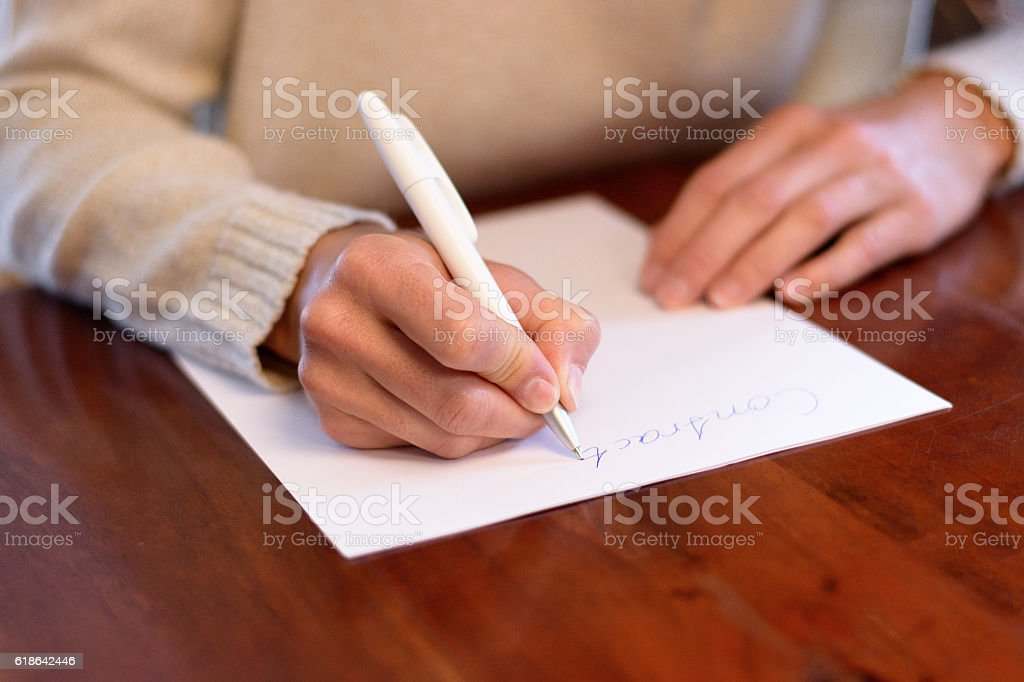 Woman sitting writing on a sheet of white paper stock photo