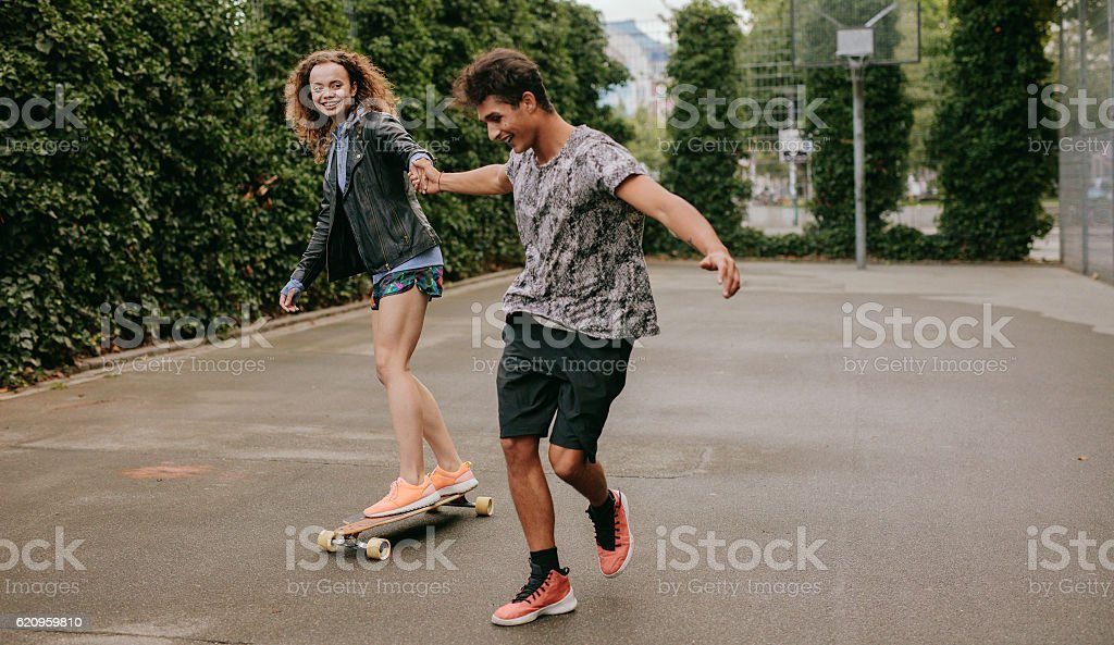 Woman skating on a basketball court with friend stock photo
