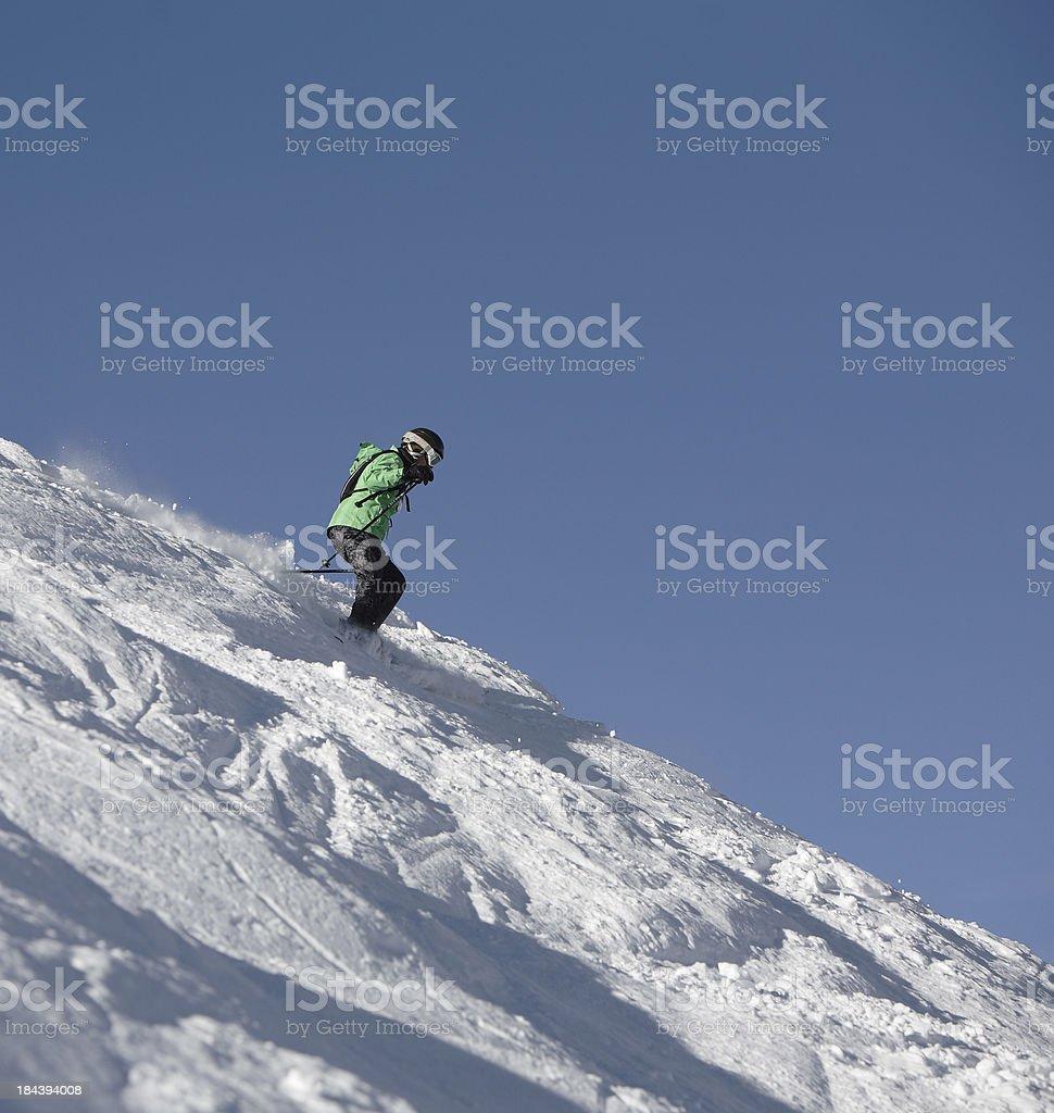 Woman skier on steep mogul slope stock photo