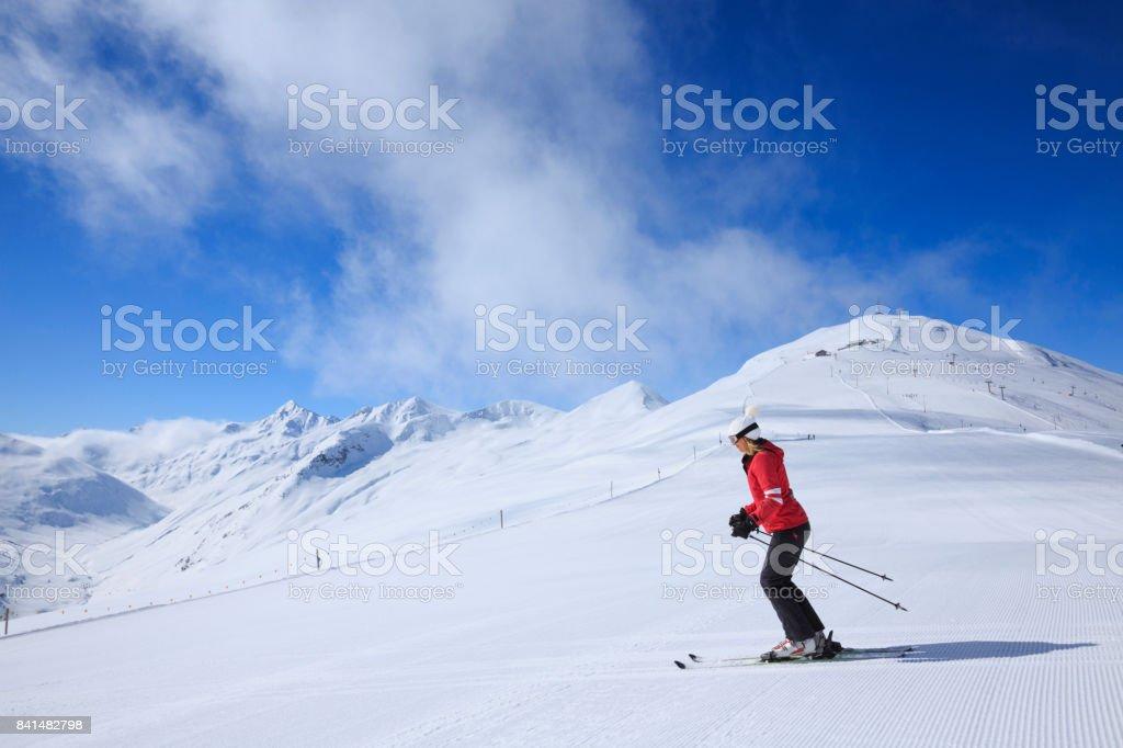 Woman skier skiing at sunny ski resort Dolomites in Italy