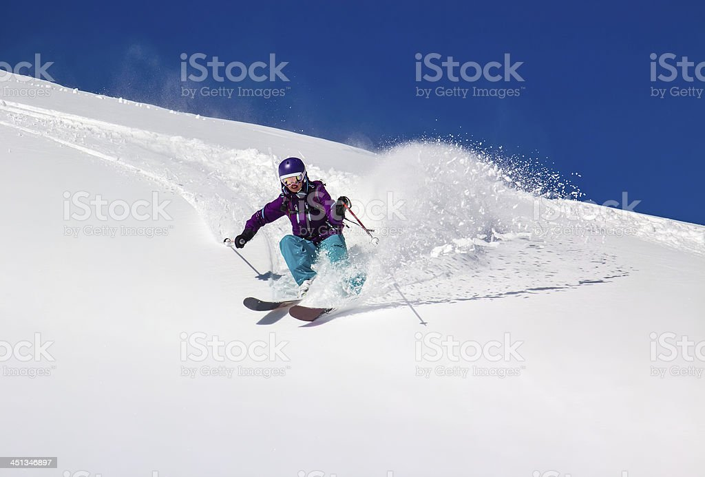 Woman Skier turns on a steep slope stock photo