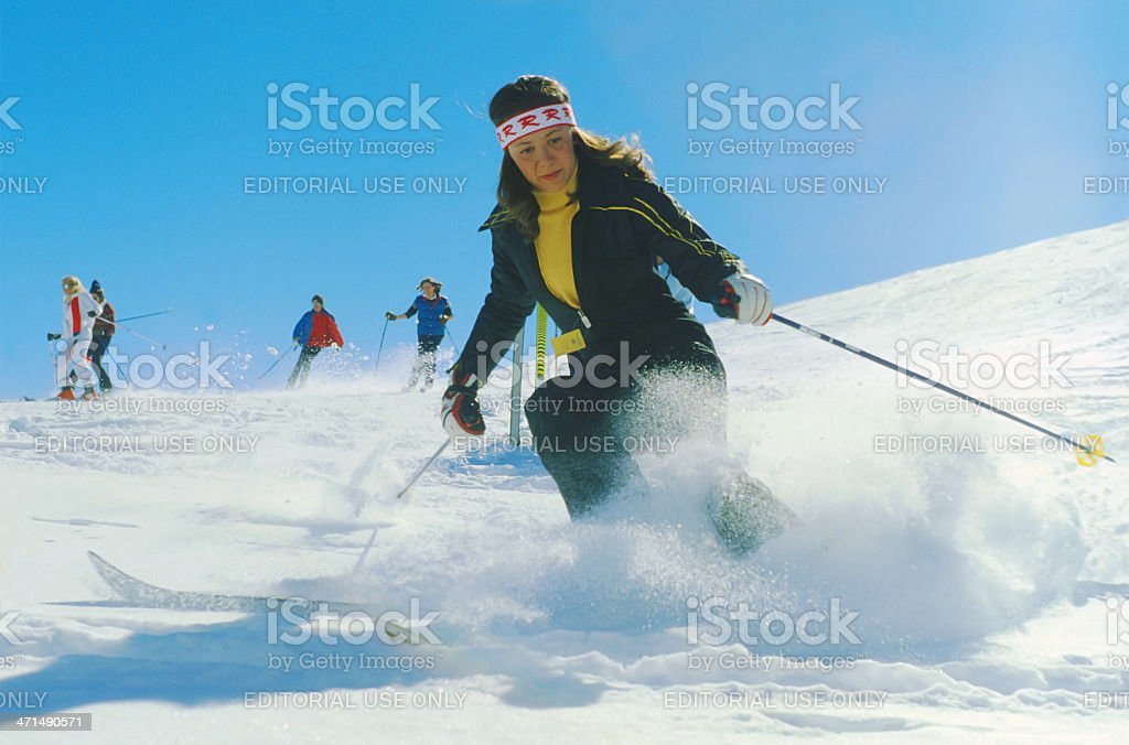 Woman skier with vintage ski suit descending from a runway royalty-free stock photo