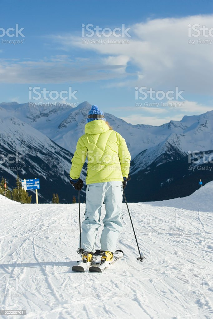 Woman skiing down slope, rear view stock photo