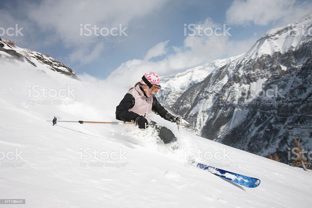 Woman skiing on steep slope stock photo