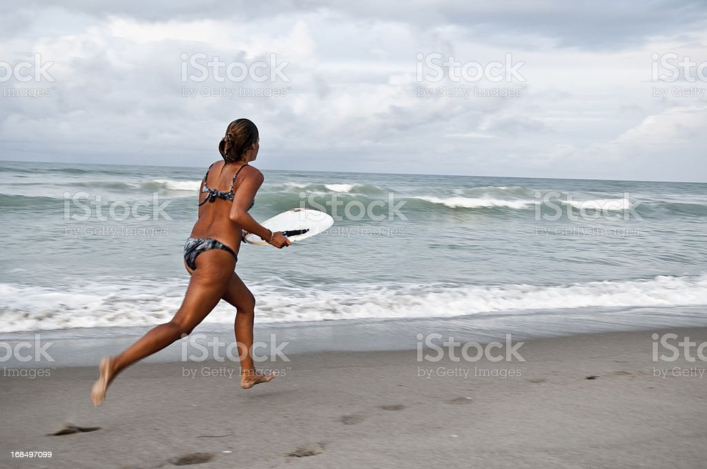 Woman skimboarding at beach in Indialantic, Florida stock photo