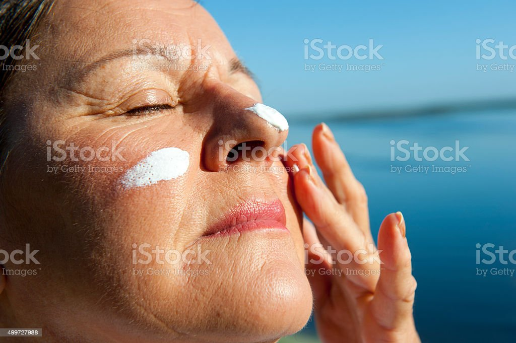 Woman Skin cancer protection suncream stock photo