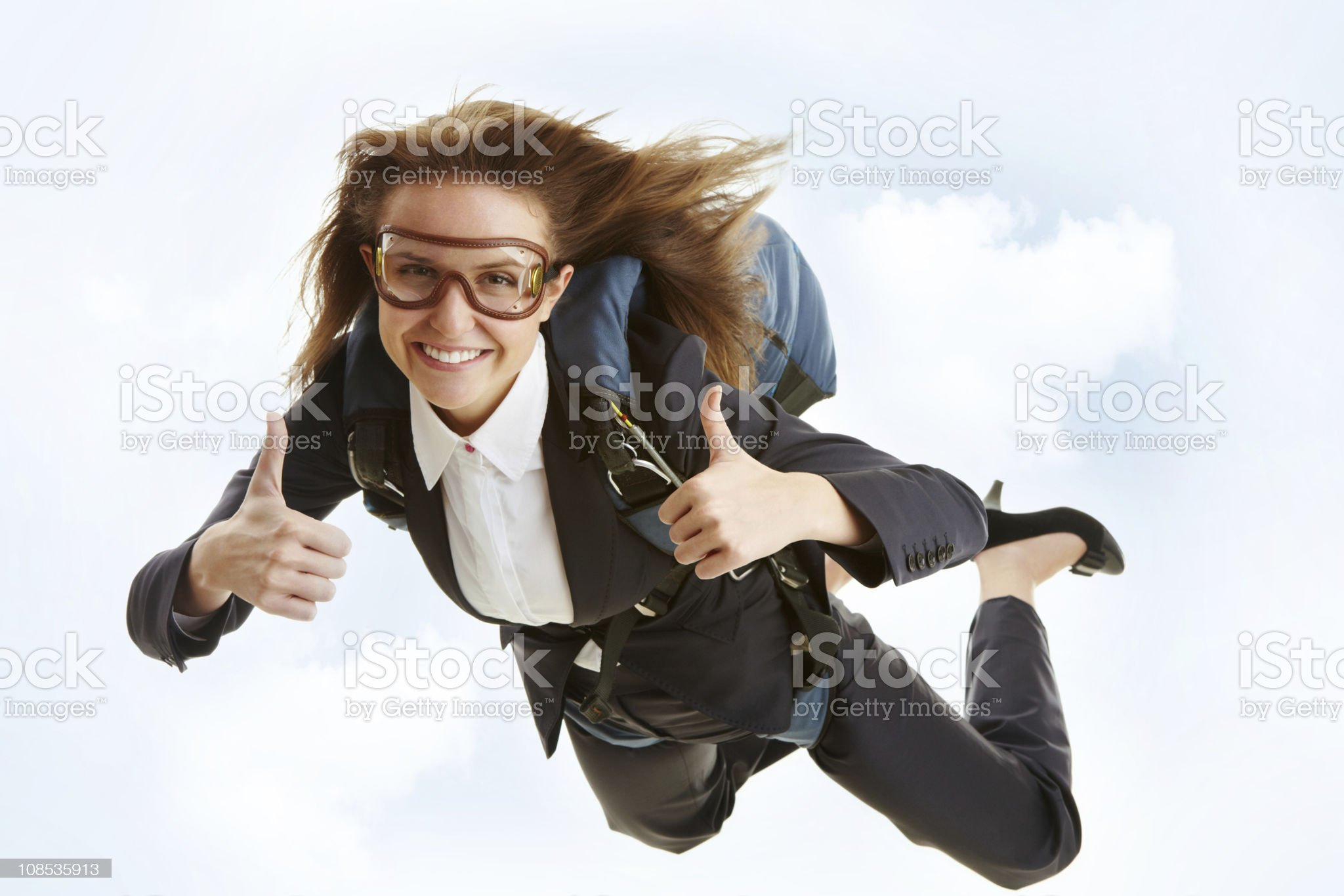 A woman skydiving in a business pantsuit and high heels  royalty-free stock photo