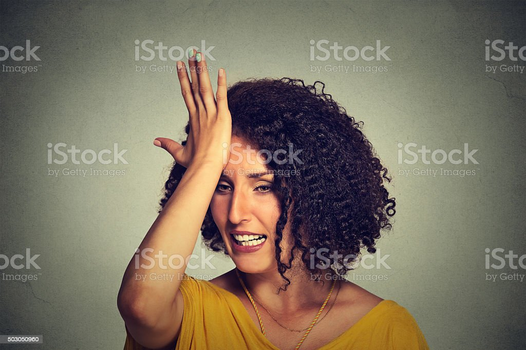 woman slapping hand on head to say duh made mistake stock photo