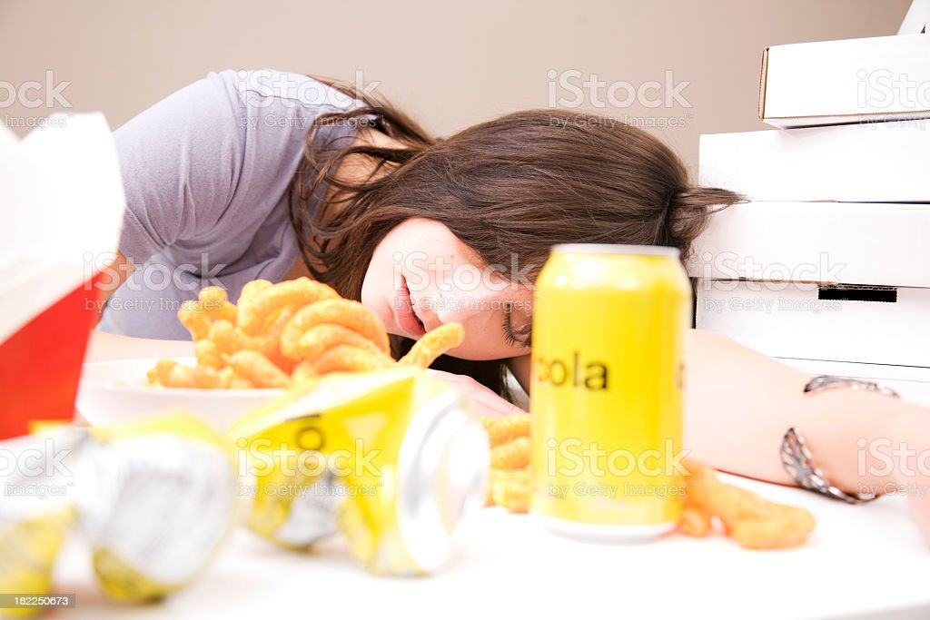 Woman sleeping after eating a lot of food stock photo
