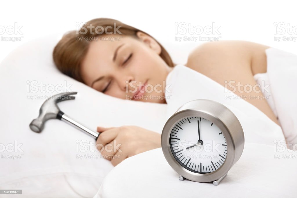 Woman sleeping and holding a hammer next to an alarm clock royalty-free stock photo