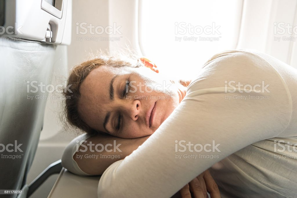 Woman Sleeping at the airplane stock photo