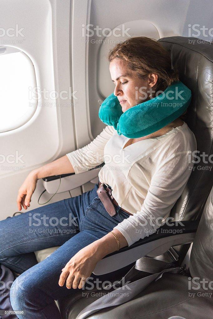 Woman Sleeping in a plane stock photo