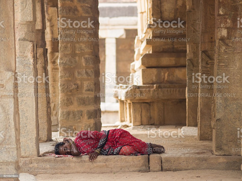 Woman sleeping in an Indian temple in Hampi, Southern India stock photo