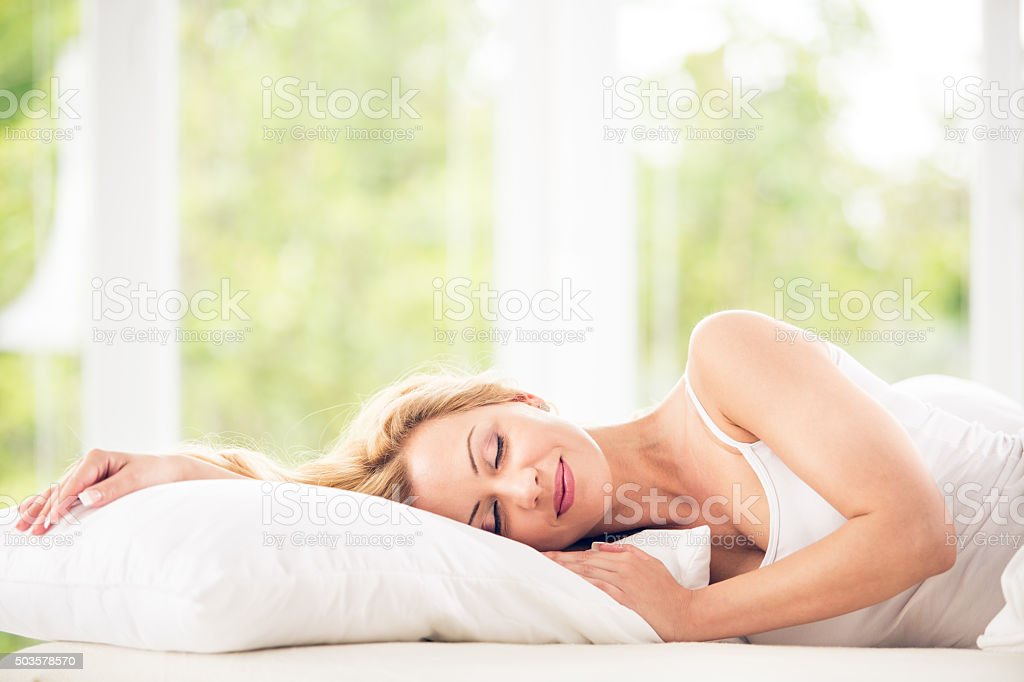 Woman sleeping in bed stock photo