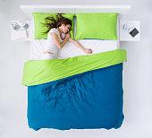 Woman sleeping in her bedroom