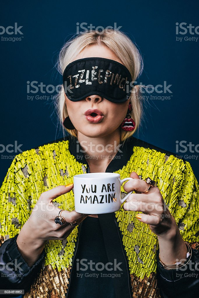 Woman sleeping mask over eyes drinking coffee stock photo