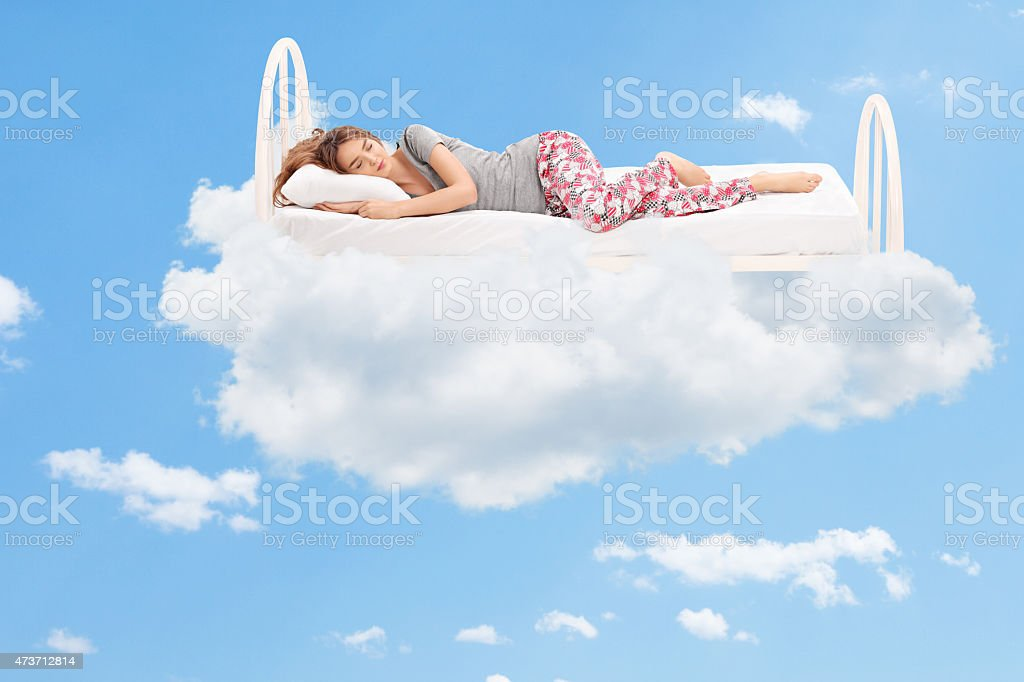 Woman sleeping on a comfortable bed in the clouds stock photo