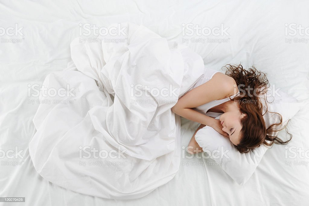 Woman sleeping peacefully in a bed with clean white sheets stock photo
