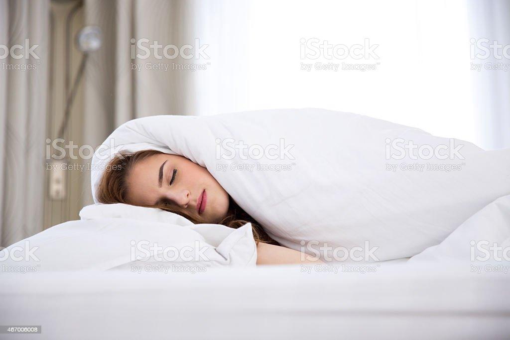 woman sleeping under a blanket stock photo