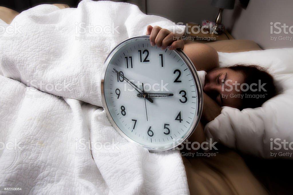 Woman sleeps holding an analog clock at 3 o'clock stock photo