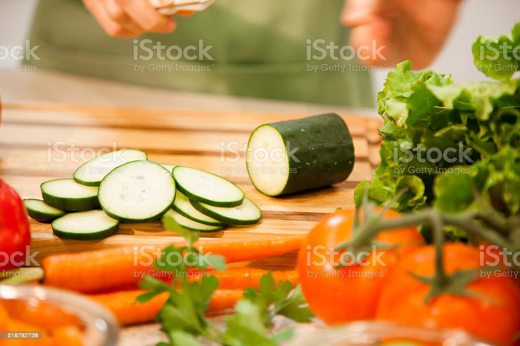 Woman slices cucumber, vegetables in home kitchen. stock photo