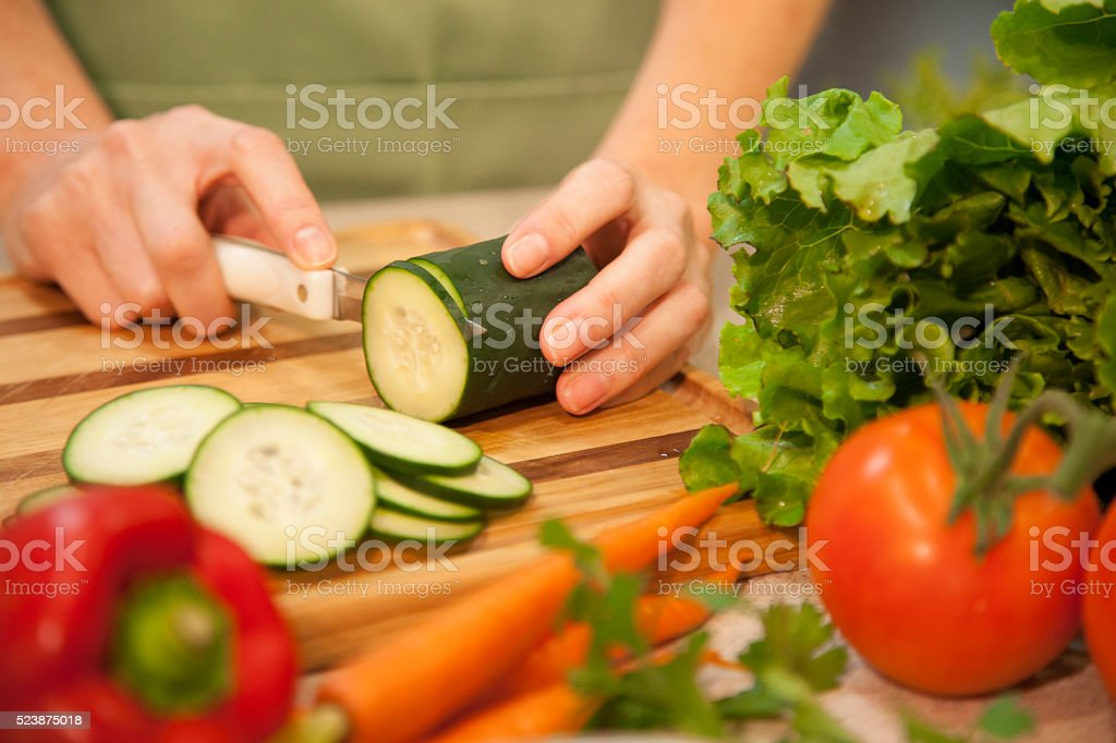 Woman slices cucumber, vegetables in home kitchen.  Salad. stock photo