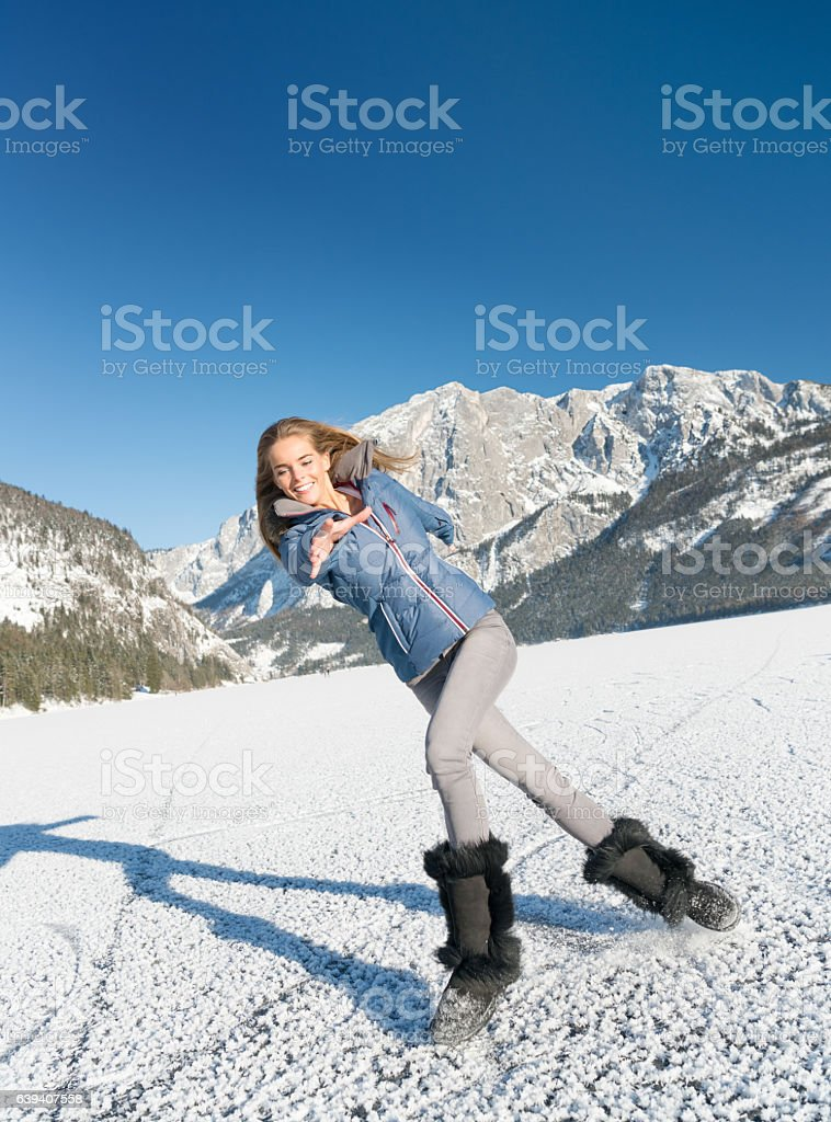 Woman sliding and slipping on ice, Frozen Lake Altaussee, Austria stock photo