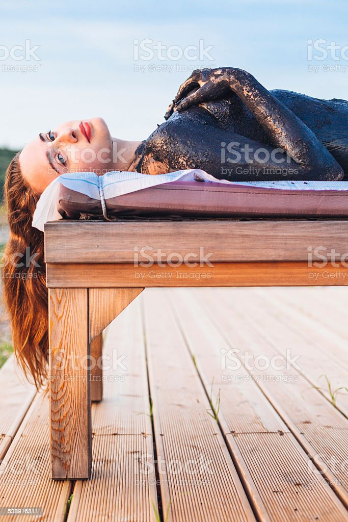 Woman sludge treatment during sunset stock photo