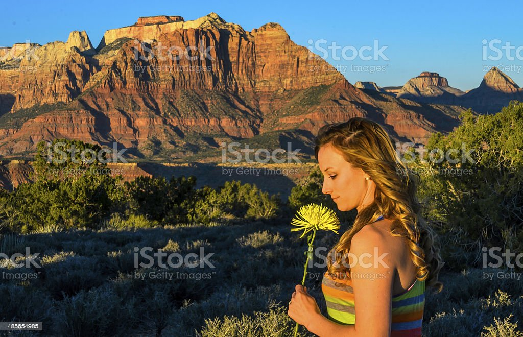 Woman smelling a desert flower on top of a mesa. royalty-free stock photo