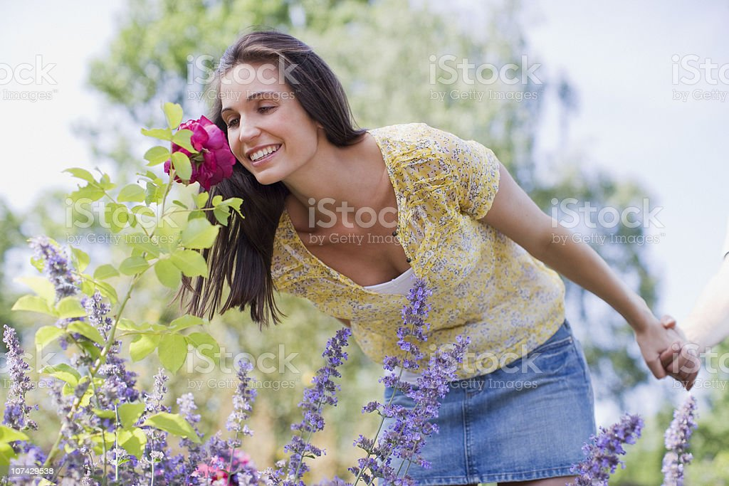 Woman smelling blooming rose in park royalty-free stock photo