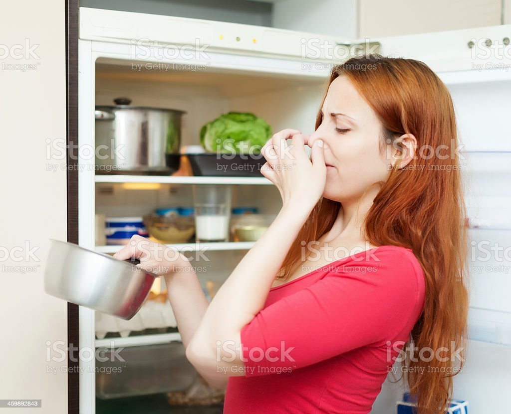 Woman smelling disgusting food and holding her nose stock photo