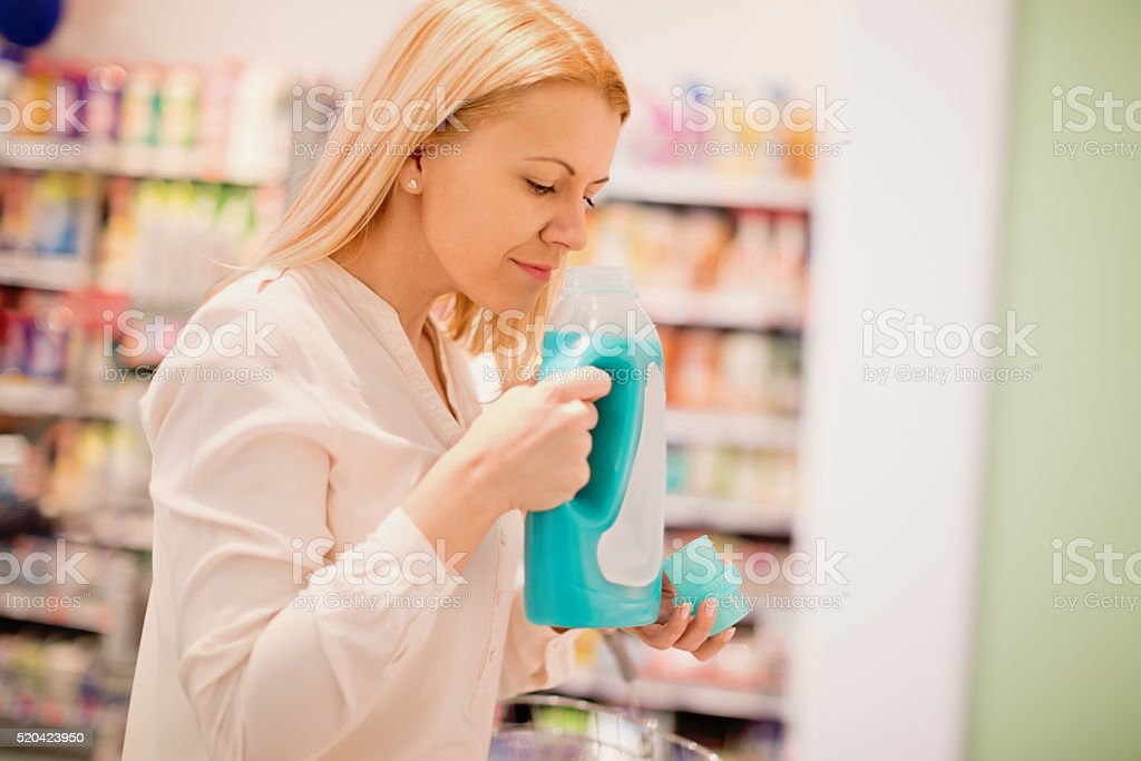 Woman smelling fabric softener stock photo