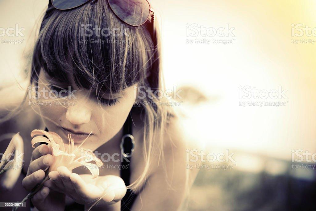 woman smelling flower in garden stock photo