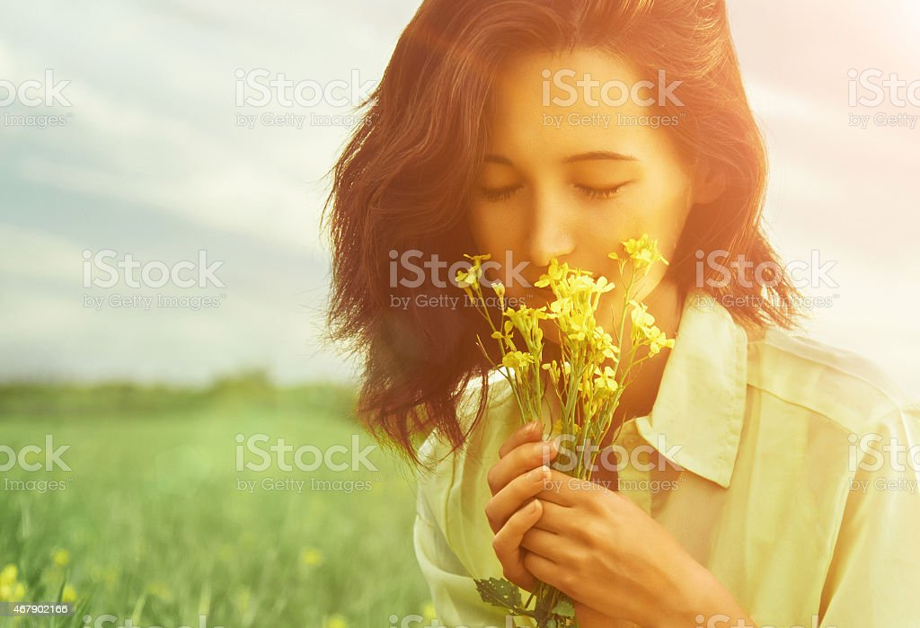 Woman smelling flowers in summer stock photo