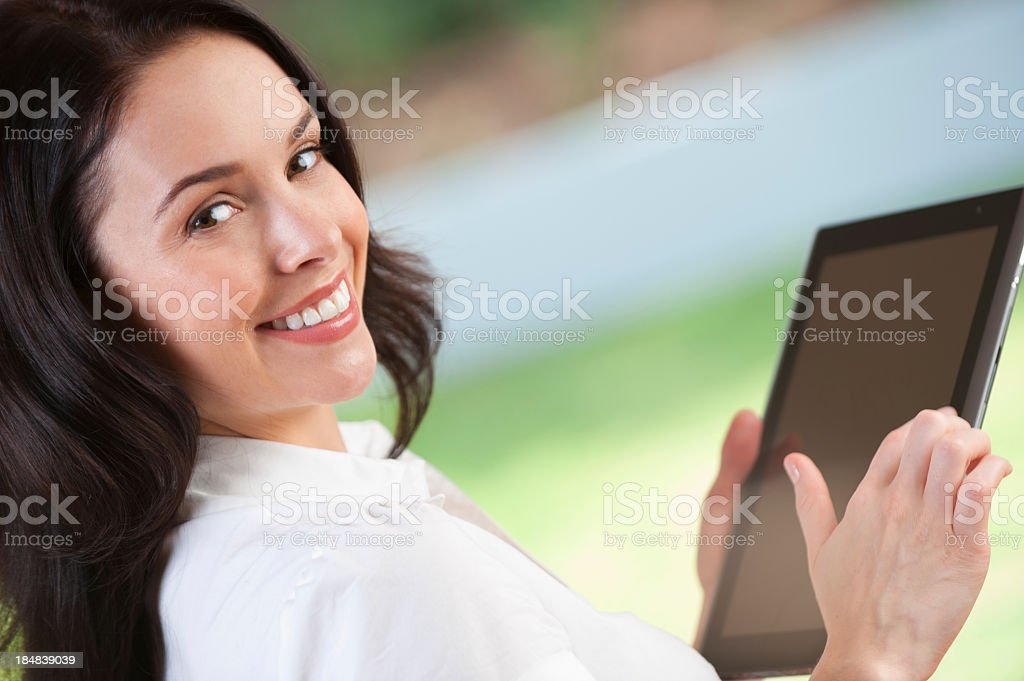 Woman smiles while holding a tablet computer royalty-free stock photo