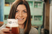 Woman smiling and holding a glass of beer