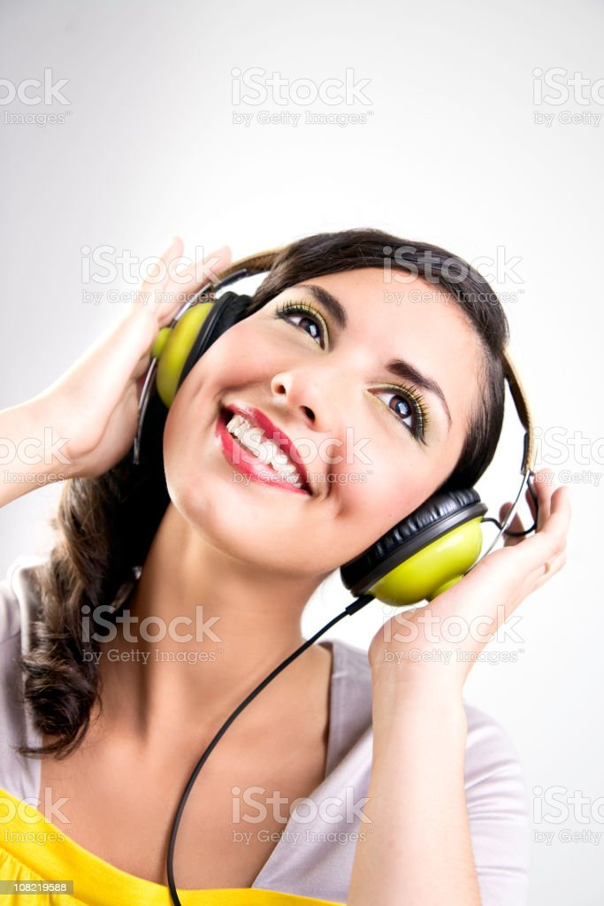 Woman Smiling and Listening to Music in Bright Colored Headphones stock photo