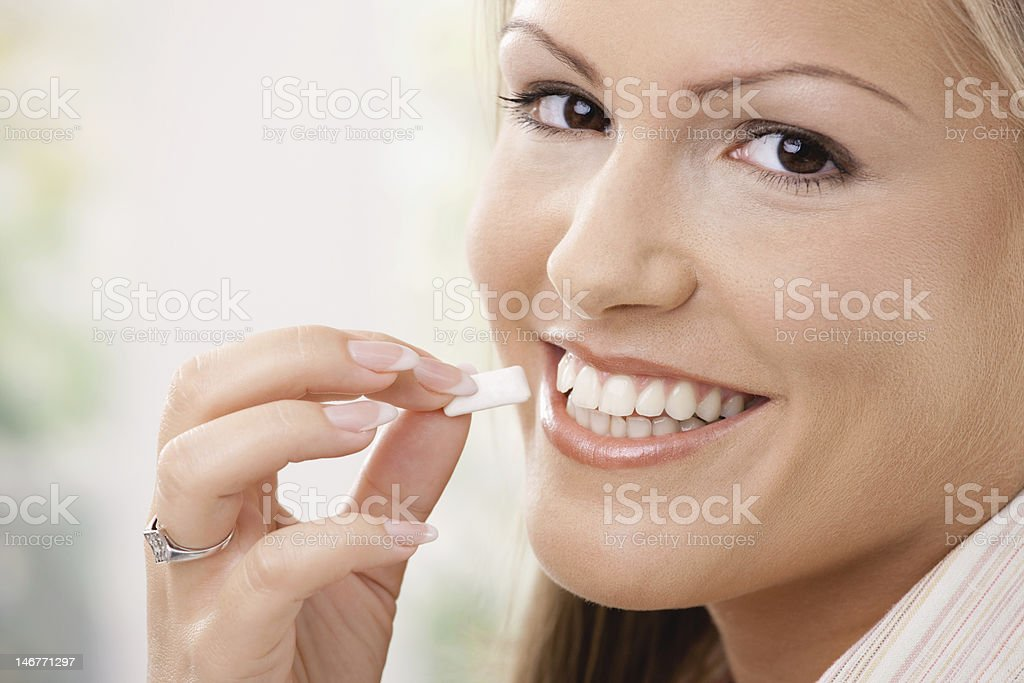 Woman smiling and placing chewing gum in mouth stock photo