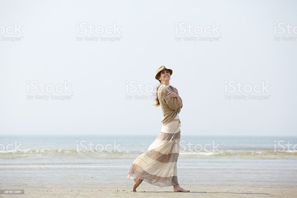 Woman smiling and walking on the beach royalty-free stock photo