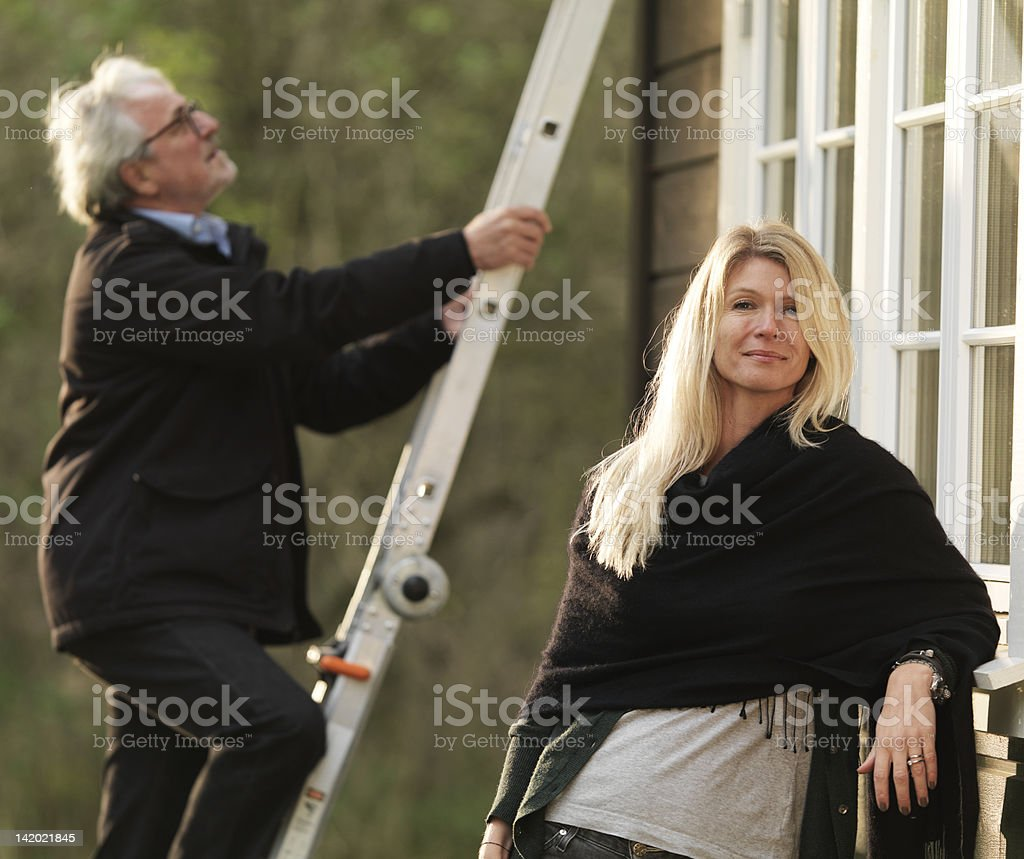 Woman smiling as husband climbs ladder stock photo