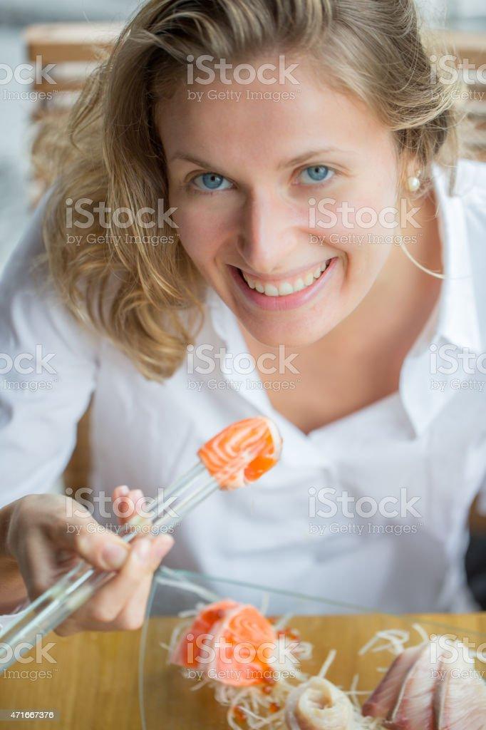 A woman smiling as she eats sushi stock photo